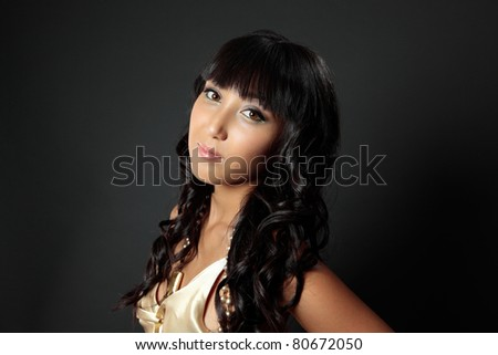 Beautiful young woman with long luscious shiny dark hair lightly curled. - stock photo