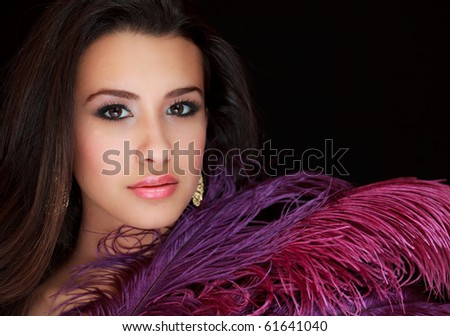 Beautiful young woman with long pink and purple feathers on a black background.