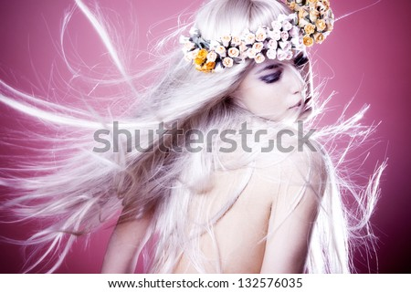 beautiful young woman with long shiny blond flying hair and wreath of flowers - stock photo