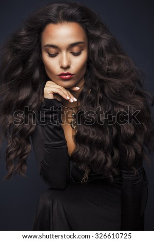 Beautiful young woman with long wavy hair and black elegant dress. Studio shot, Vertical - stock photo