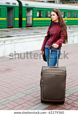 Beautiful young woman with luggage is waiting a train - stock photo