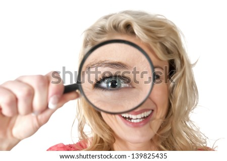 beautiful young woman with magnifying glass - stock photo
