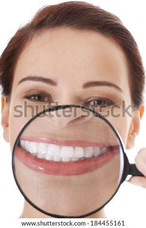 Beautiful young woman with magnifying glass on mouth. Isolated on white. - stock photo