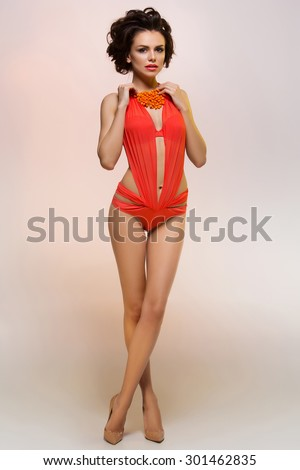 Beautiful young woman with makeup and hairdo standing in fashionable orange swimsuit
