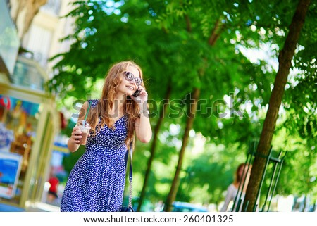 Beautiful young woman with mobile phone in the street on a summer day - stock photo