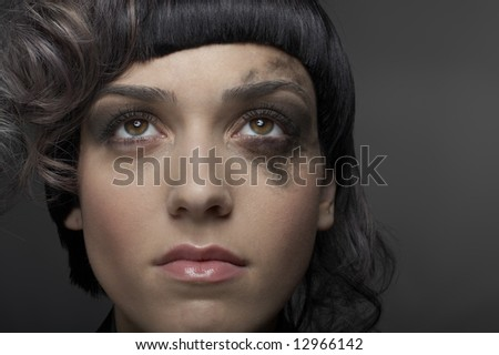 Beautiful young woman with moody light over gray background
