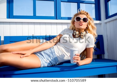 Beautiful young woman with music headphones and take away coffee cup, lying on the bench and waiting for a water taxi.