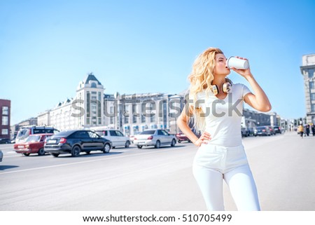 Beautiful young woman with music headphones drinking from a take away coffee cup and posing against urban city background.