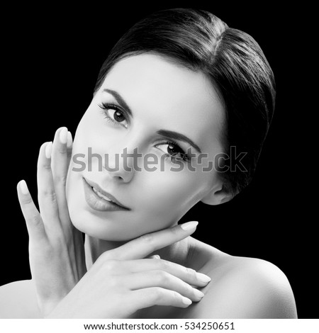Beautiful young woman with naked shoulders, isolated against black background. Brunette model - beauty, glamour, fashion, modeling, cosmetics, health skin and body care concept. Black and white.