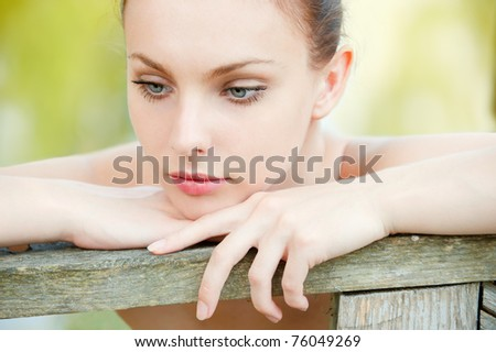 Beautiful young woman with naked shoulders leans against wooden handrail in city park.