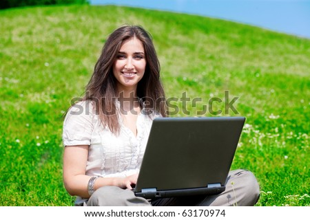 Beautiful young woman with notebook sit on hill