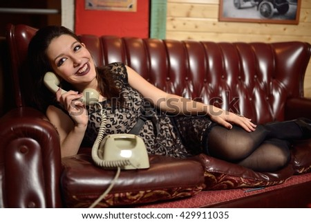 beautiful young woman with old phone vintage style