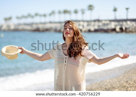 Beautiful young woman with open arms deep breathing in the beach.