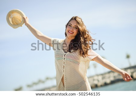 Beautiful young woman with open arms smiling in the beach. Girl with sun hat in summer.