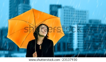 Beautiful young woman with orange umbrella on rainy day - stock photo