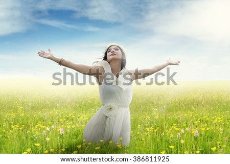 Beautiful young woman with outstretched hands enjoying freedom on the meadow in springtime