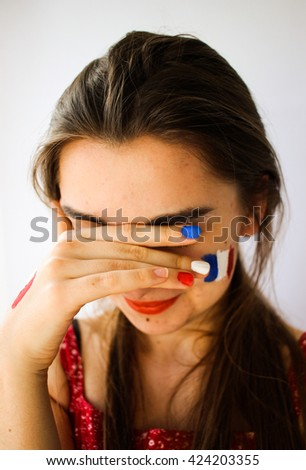 Beautiful young woman with painted french flag on face, hand & manicure, olympic games supporter - stock photo