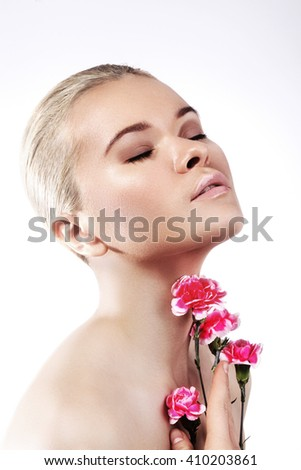 Beautiful young woman with perfect clean shiny skin, natural fashion makeup. Close-up woman, fresh spa look,the gentle young woman with flowers - stock photo