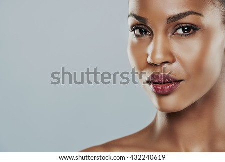Beautiful young woman with perfect skin against a gray background - stock photo