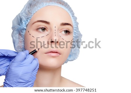Beautiful young woman with perforation lines on her face before plastic surgery operation. Beautician touching woman face and draws a pencil or marker. studio shot on a white background - stock photo