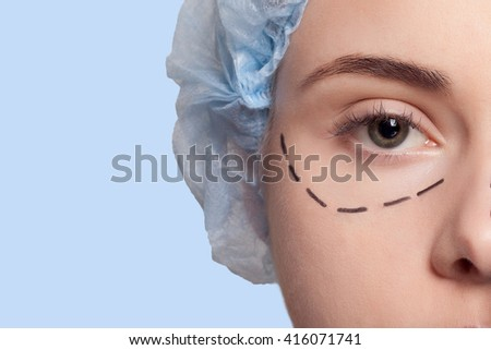 Beautiful young woman with perforation lines on her face before plastic surgery operation. Beautician touching woman face and draws a pencil or marker. concept of beauty - stock photo