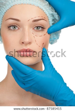 Beautiful young woman with perforation lines on her face before plastic surgery operation. Beautician touching woman face. - stock photo