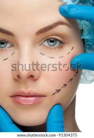 Beautiful young woman with perforation lines on her face before plastic surgery operation. Beautician touching woman face.
