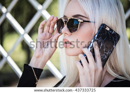 Beautiful young woman with phone outdoor - stock photo