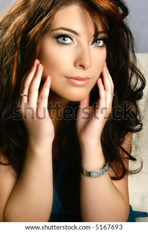 Beautiful young woman with piercing blue eyes, against neutral gray background. - stock photo