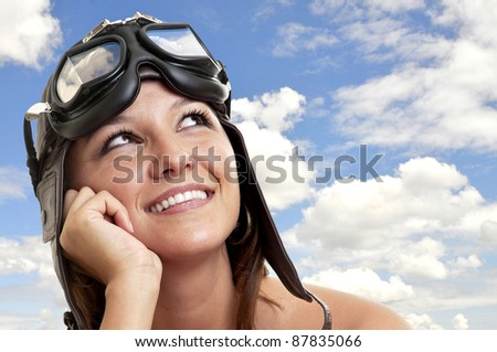 Beautiful young woman with pilot hat and goggles dreaming - stock photo