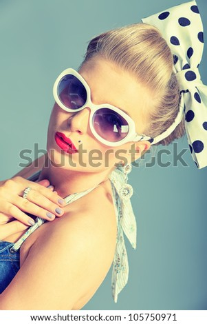 Beautiful young woman with pin-up make-up and hairstyle posing in studio. - stock photo