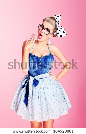 Beautiful young woman with pin-up make-up and hairstyle posing over pink background. - stock photo