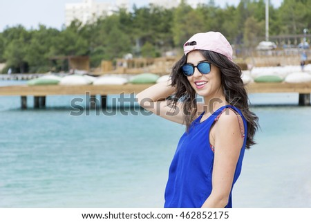 beautiful young woman with pink hat  on the beach.Summer holiday