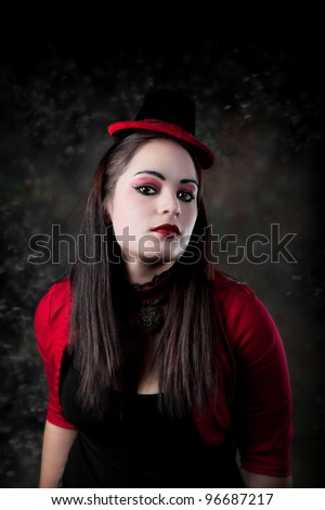 Beautiful young woman with red eyeshadow and red lips, wearing a red sweater and a hat with red trim.