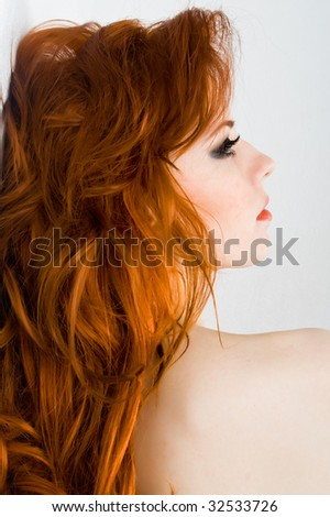 Beautiful young woman with red hair - stock photo