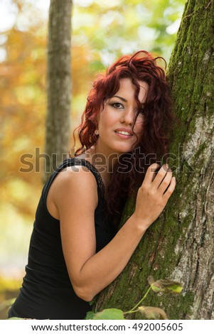 Beautiful young woman with red hair in the park