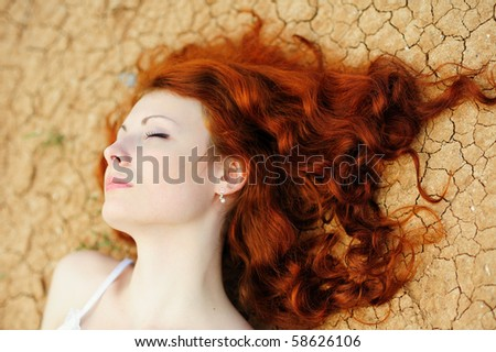 Beautiful young woman with red hair on the dried up ground - stock photo
