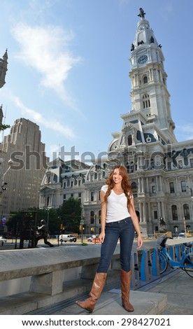 Beautiful young woman with red hair stands in white shirt and blue jeans in city  - stock photo