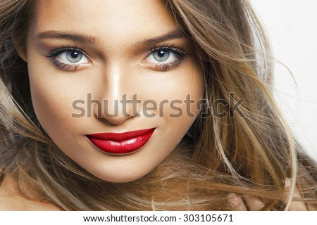 Beautiful young woman with red lips and clean skin. Studio shot, white background.  Toned in warm colors. Cosmetics  concept. - stock photo