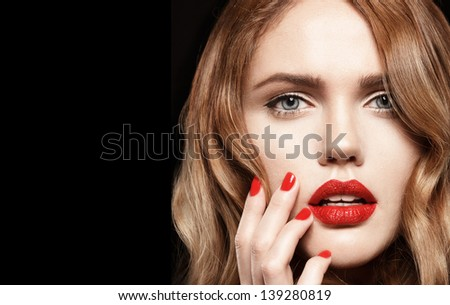 Beautiful young woman with red lips and colorful manicure