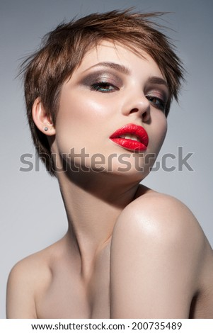 beautiful young woman with red lips, shot hair. Trendy evening make-up - stock photo