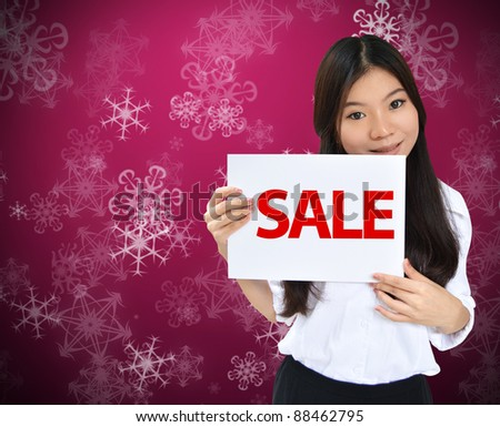 Beautiful young woman with sale text over Christmas background - stock photo