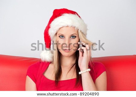 Beautiful young woman with santa hat calling with cellphone - stock photo