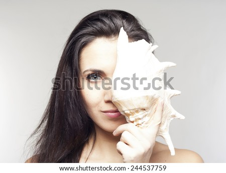 Beautiful young woman with sea-shell - stock photo