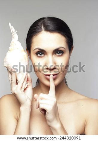 Beautiful young woman with sea-shell saying shh - stock photo