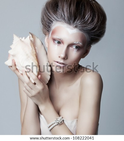 Beautiful young woman with seashell posing isolated. Series of photos - stock photo