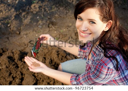 Beautiful young woman with seeds in her hand - stock photo
