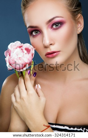 Beautiful young woman with sensitive makeup holding peony in her hand on blue background, close up. Fashion photo.