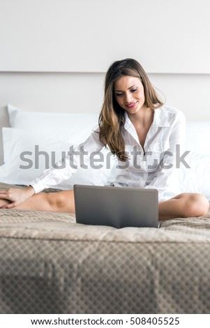 Beautiful young woman with sexy long legs in shirt using a notebook in bed