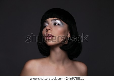 Beautiful young woman with shining silver face makeup - stock photo